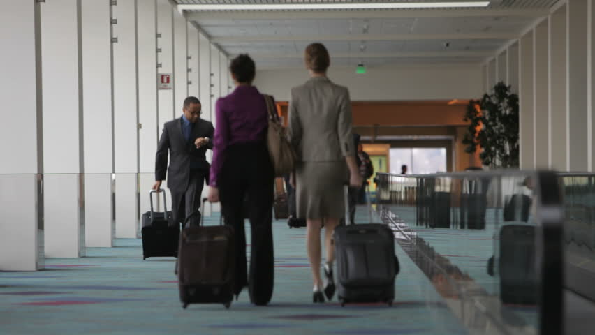Business man runs through airport checking watch