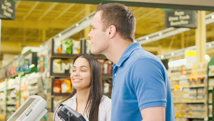 Couple walk through check out counter and exchange smiles with the cashier. Medium shot.