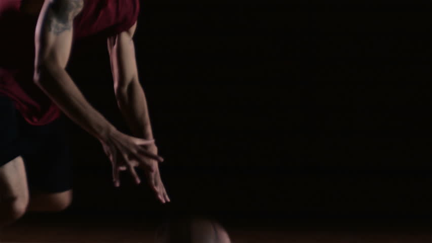 A basketball player runs up and does a trick dunk by himself