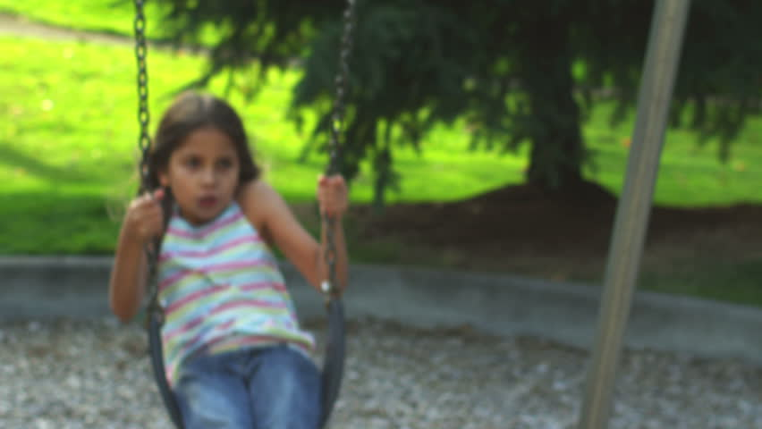 Adorable little girl on a swing smiles for the camera. Medium shot.