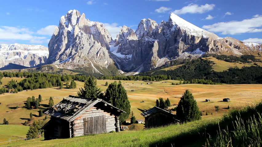 Beautiful Alpine pasture with wooden lodges beneath the forbidding rocky peaks of the Italian Dolomites in Seiser Aim, Italy - HD stock footage clip