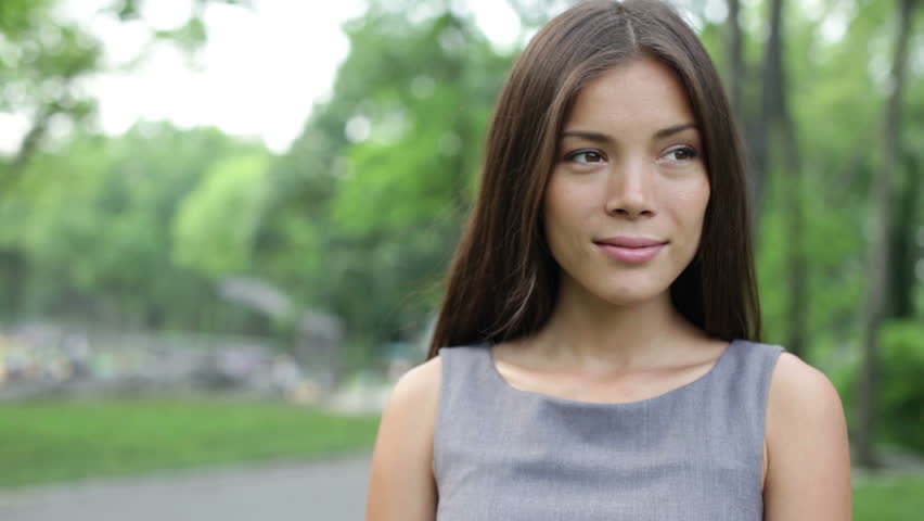 Businesswoman portrait standing looking around smiling happy in New York City, Central Park. Young Asian female professional outdoor portrait closeup in Manhattan, USA. - HD stock footage clip