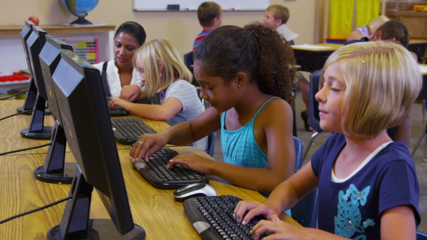 Elementary school teacher helps students with computers