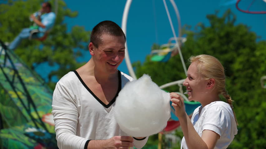Funny couple eating cotton candy.