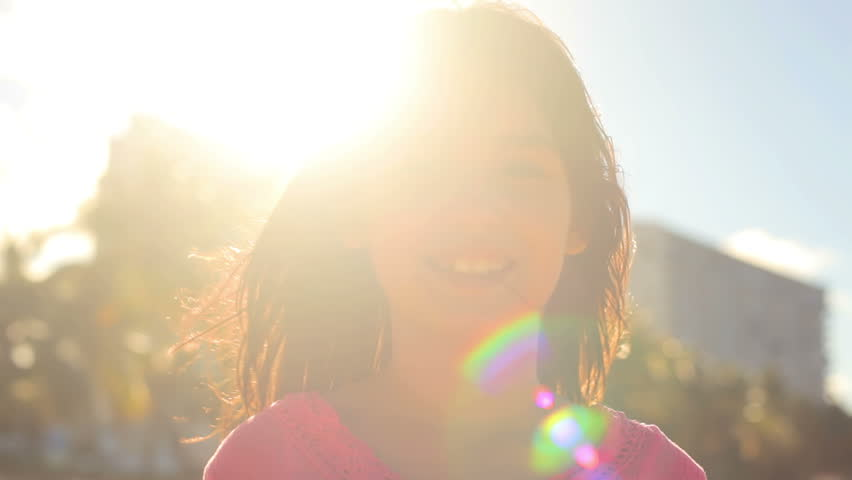 A young girl smiles at the camera with the sun behind her while at the beach