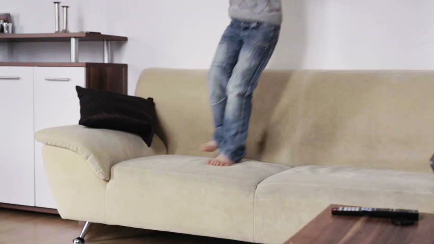 1 kid playing and jumping on the couch at home in the living room in the daytime