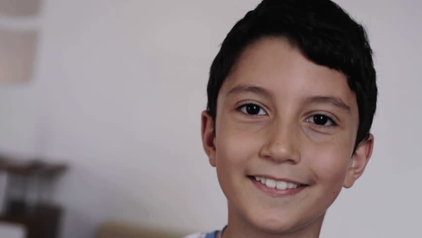 close up of young european boy smiling at home in the living room
