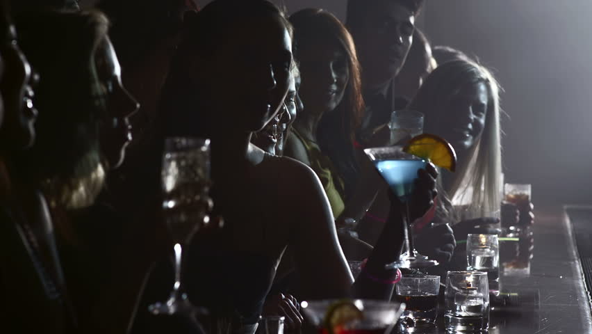 Dark shot of a row of people drinking at a bar