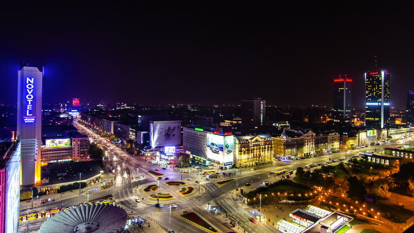 Night cityscape of Warsaw city centre in a time lapse, cars quickly passing, city lights on, neons, large adverts, main roundabout, Novotel hotel and Marriott hotel sky scrapers, 1st October 2013
