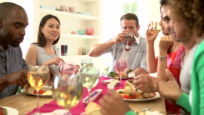 Group of friends around a table eating and talking at dinner party together - HD stock footage clip