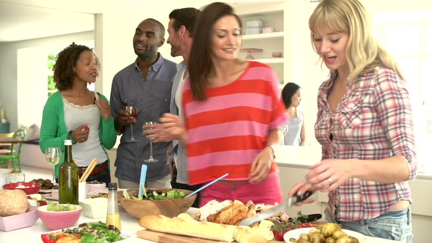Group of friends eating, talking, and drinking in kitchen before a delicious buffet at a dinner party - HD stock video clip