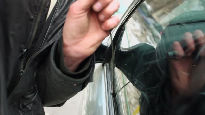 man in leather jacket tries to break door lock of car by. Black Bedroom Furniture Sets. Home Design Ideas