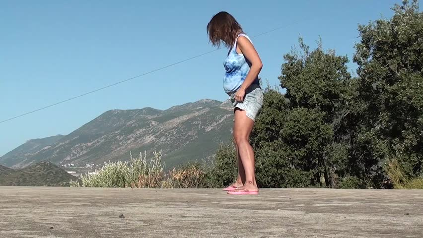 A pregnant woman does gym outdoors – leg-split with bends back and forward, sidewise - HD stock video clip