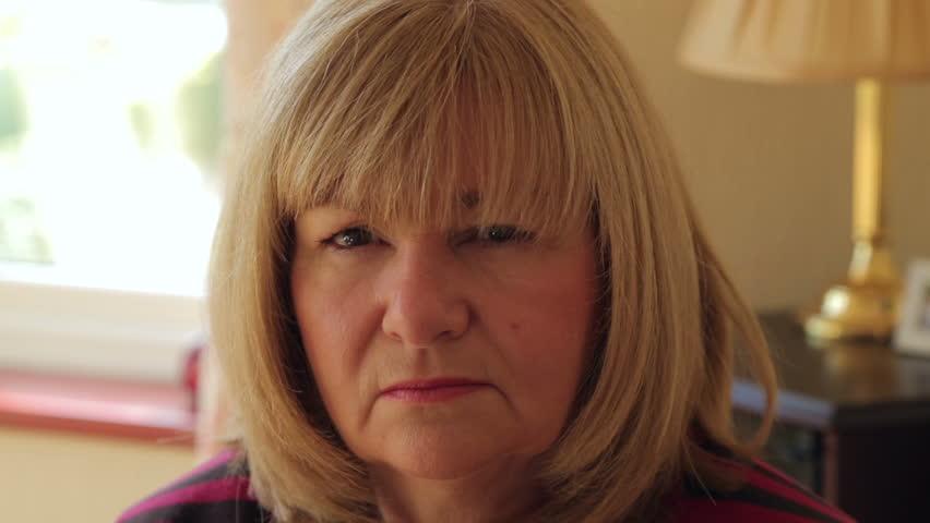 Senior woman turns to camera and shakes head, no