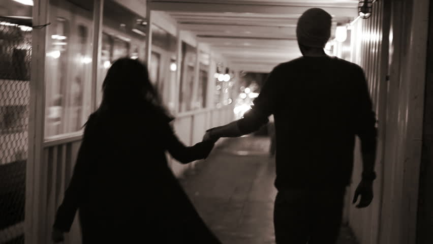 A couple holds hands as they walk down a tunnel at night in the city. Black and white shot