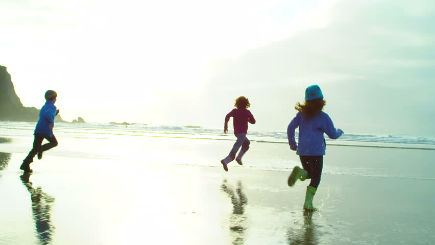 Three kids run down the beach with a bright sun shining on them and the coast