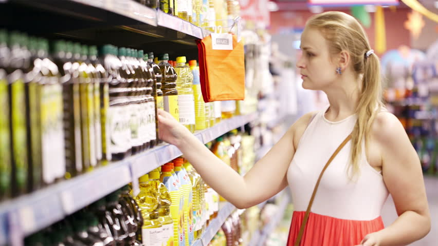 Young blond woman picking an olive oil bottle from the shelves of a supermarket and reading the label