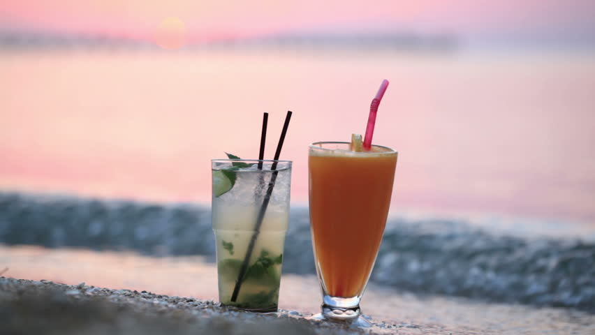 Close up shot of two fruity alcoholic cocktails mojito and orange juice standing side by side in their tall glasses in the sand on tropical beach at sunset against a colourful pink sky in the evening