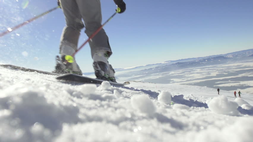 Slow motion of back country skier skiing down the snowy