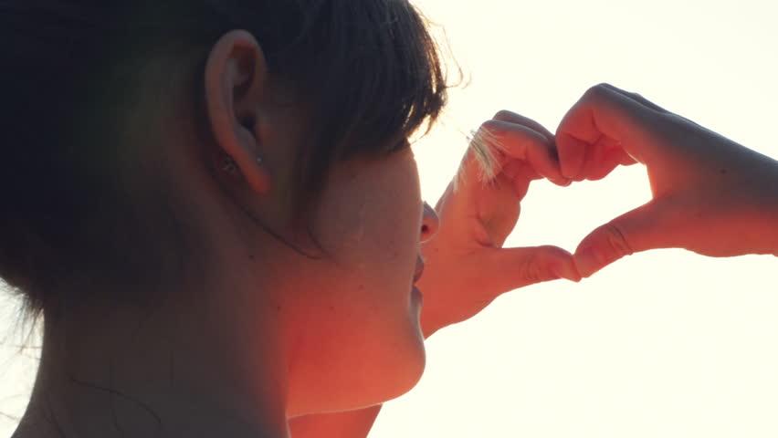 female hands making heart shape gesture holding sun flare