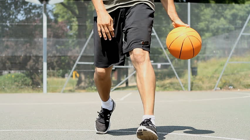 Basketball player rapidly bouncing the ball between his legs skilfully