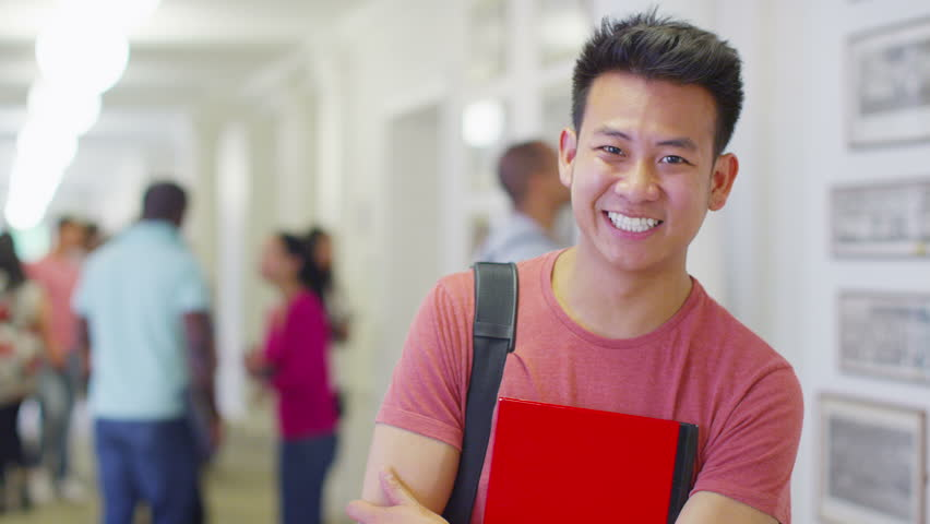 Portrait of a happy male asian student standing in a  busy hallway with other students and teachers walking in the background. In slow motion.