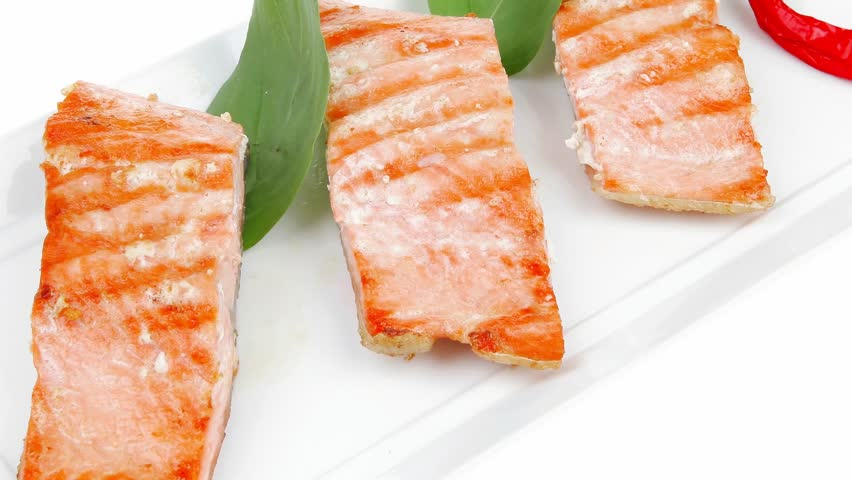 roasted salmon pieces with pepper and lemon on basil leaf over ceramic plate 1920x1080 intro motion slow hidef hd