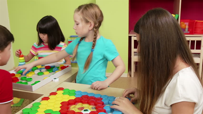 Cute preschoolers and their teacher making a puzzle picture with colorful pieces