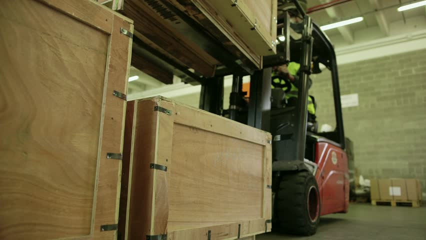 Logistics business and shipping facility with manual worker operating forklift to move boxes and goods, man working in warehouse, worker in industry. 11of19