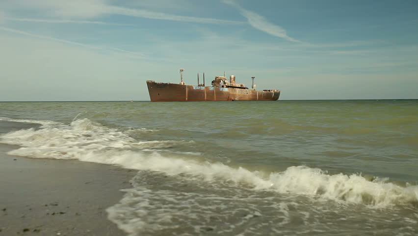 Waves wash shore. Wreck ship background. - HD stock video clip