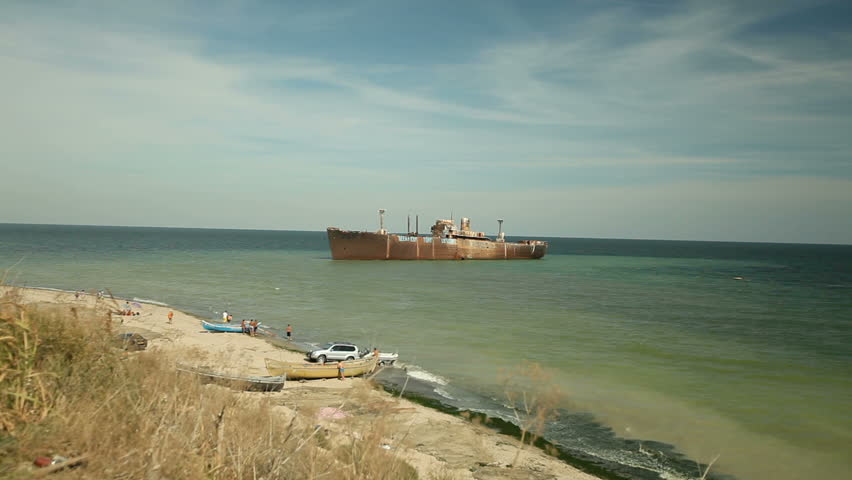 Waves wash shore. Wreck ship background. - HD stock footage clip