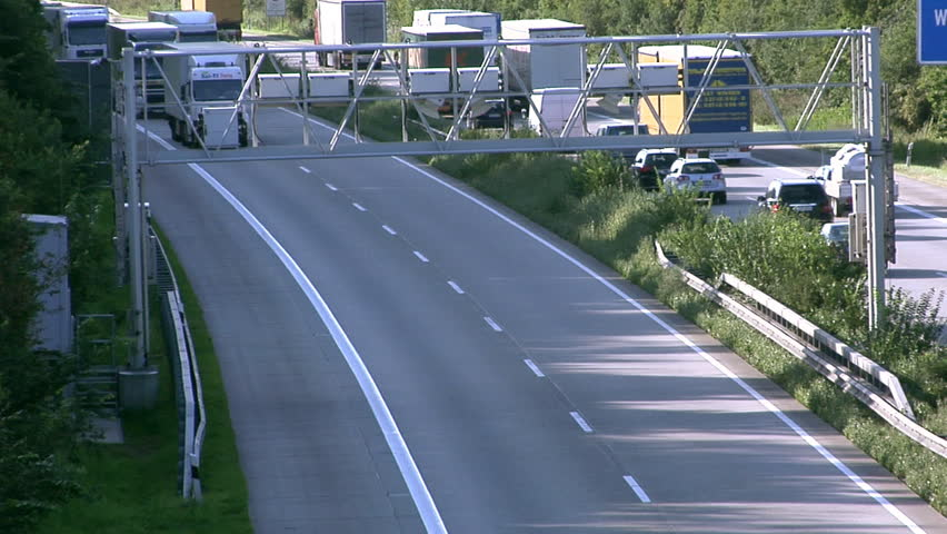 Lots of trucks passing under a toll collecting device on a German Autobahn (motorway).  - HD stock video clip