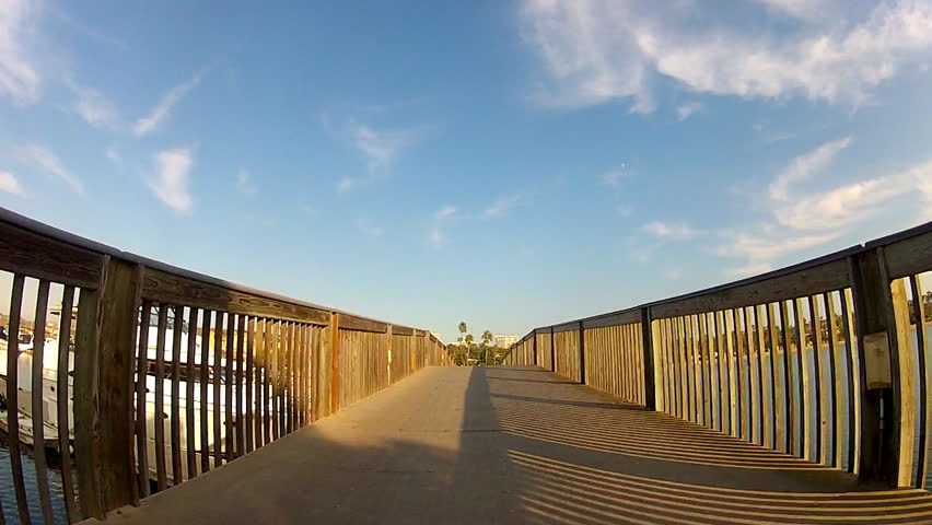First person view of man riding a bicycle on a wooden bridge next to a marina in Newport Beach, California. This clip features a shadow of himself and his bike cast on the bridge railings next to him. - HD stock video clip
