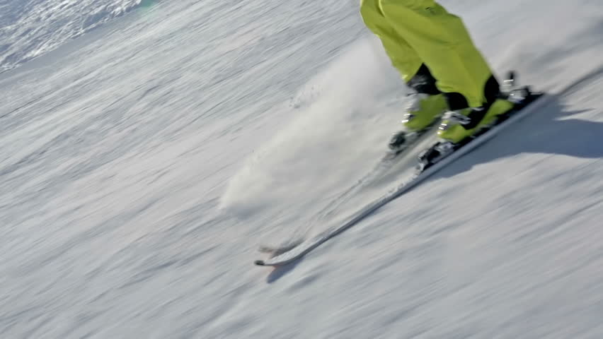 closeup alpine skier skiing in short swings on ski run