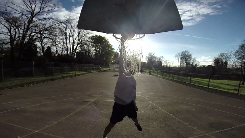 Basketball player slam dunking the ball on an outdoor basketball court - HD stock video clip