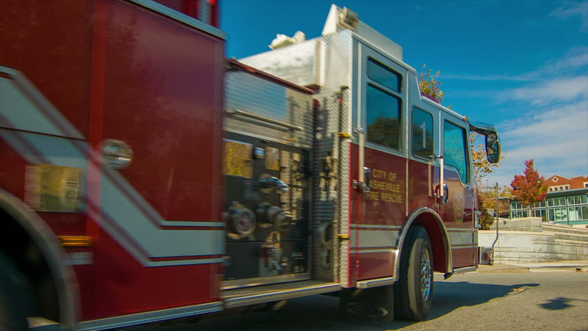 An Asheville, NC Fire Truck Driving Around a City Street Corner on a Sunny Fall Morning with a Blue Sky and Fall Colored Foliage. - HD stock footage clip