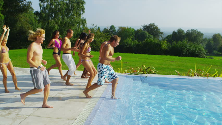 Happy fun loving group of friends running, jumping and diving into swimming pool at a pool party. In slow motion. - HD stock footage clip