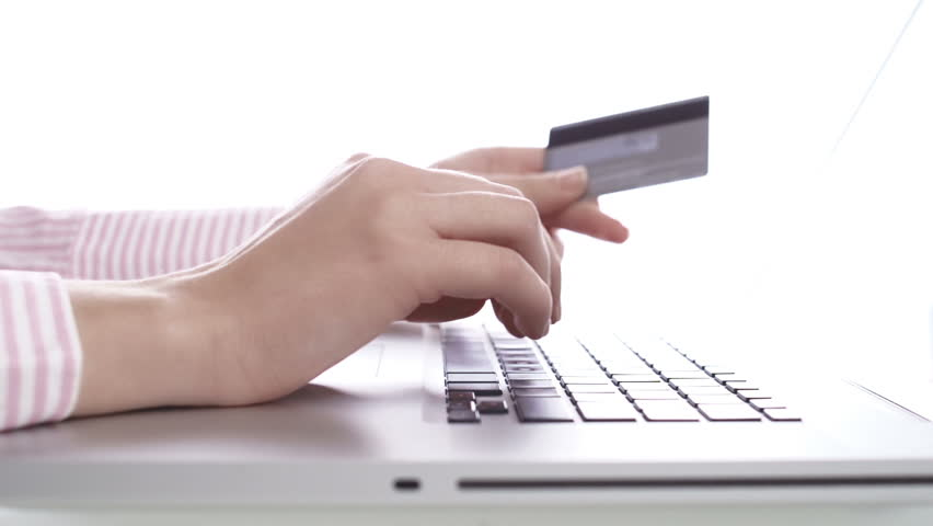 Woman buying with credit card, using laptop computer.