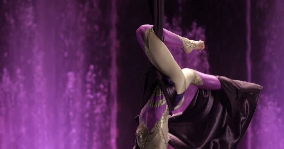 4K footage of Female gymnast performing on aerial silk in circus. Exciting acrobatic show.