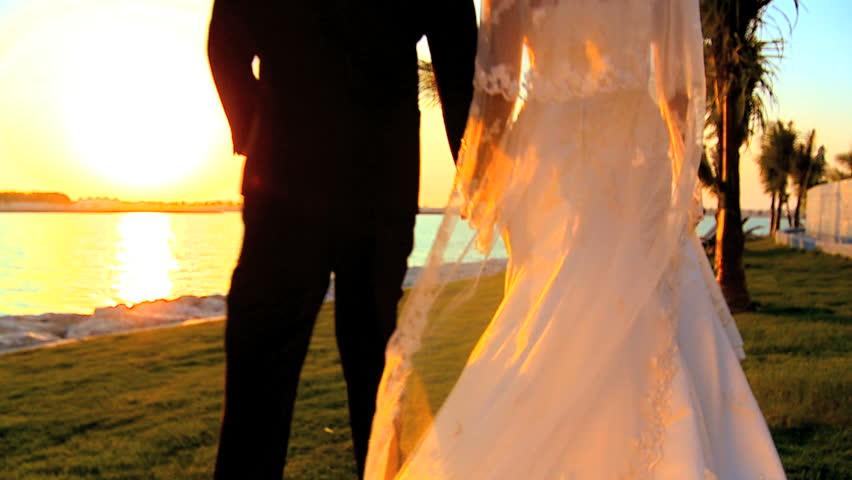 Young couple walking the beach after their tropical wedding ceremony - HD stock video clip