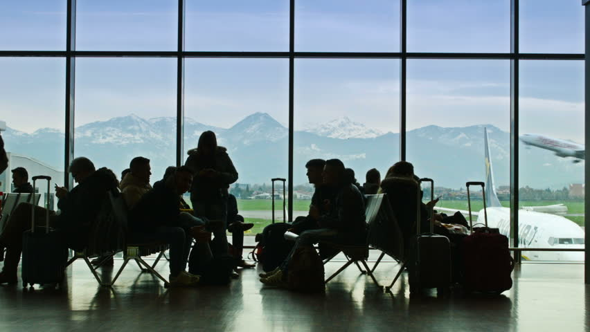BERGAMO, ITALY - NOVEMBER 23, 2013. BERGAMO, ITALY - NOVEMBER 23, 2013. Orio al Serio Airport. Passengers waiting to embark. A plane is taking off on the background.
