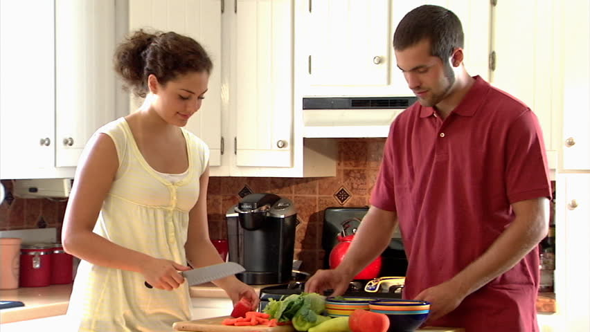 A young couple prepares a salad in the kitchen. - HD stock video clip