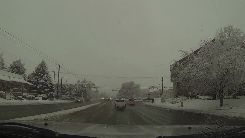 Winter driving snow storm urban city POV HD. Winter snow storm hit West and Midwest USA with extreme cold weather and snow. Dangerous driving conditions on snow packed and icy roads and highways. - HD stock video clip
