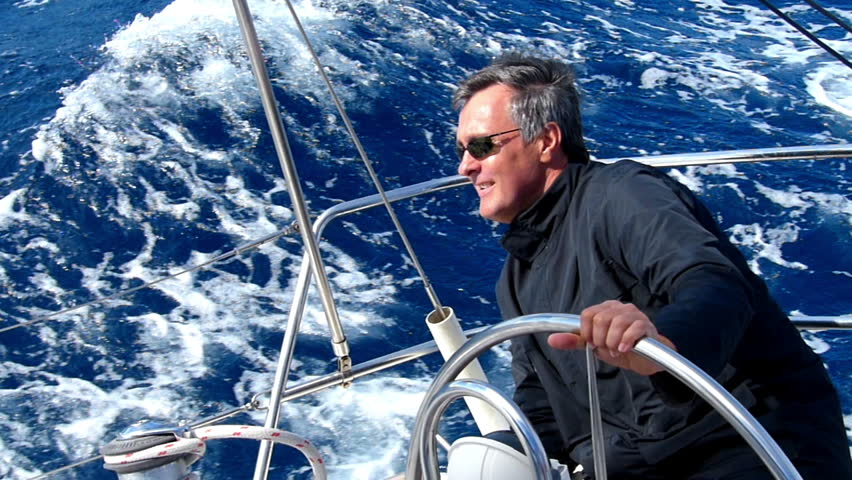 Mature adult skipper driving a sailboat. Slow motion and High speed camera.