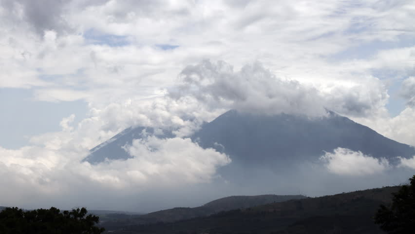 A time-lapse shot of clouds engulfing two separate volcano peaks in Antigua, Guatemala. The clouds move quickly and envelop the peaks.