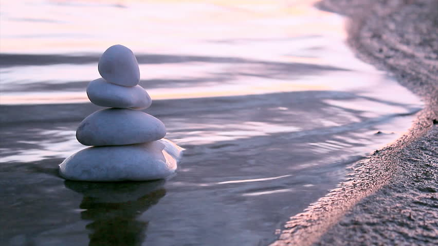 Stack of round smooth marble stones in Zen style and sea waves background - HD stock footage clip