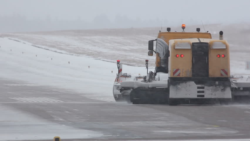 Machine removing snow off the runway of an airfield
