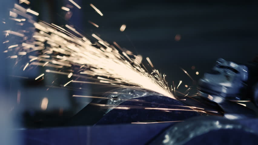 Close-Up of Grinding Heavy Industry Worker. Wearing Hardhat and Protective Headphones. Sparks on Background. Shot on RED Digital Cinema Camera in 4K, ultra-high definition, UHD