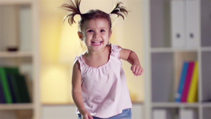 Slow-motion of a cheerful little cutie jumping happily at home - HD stock footage clip