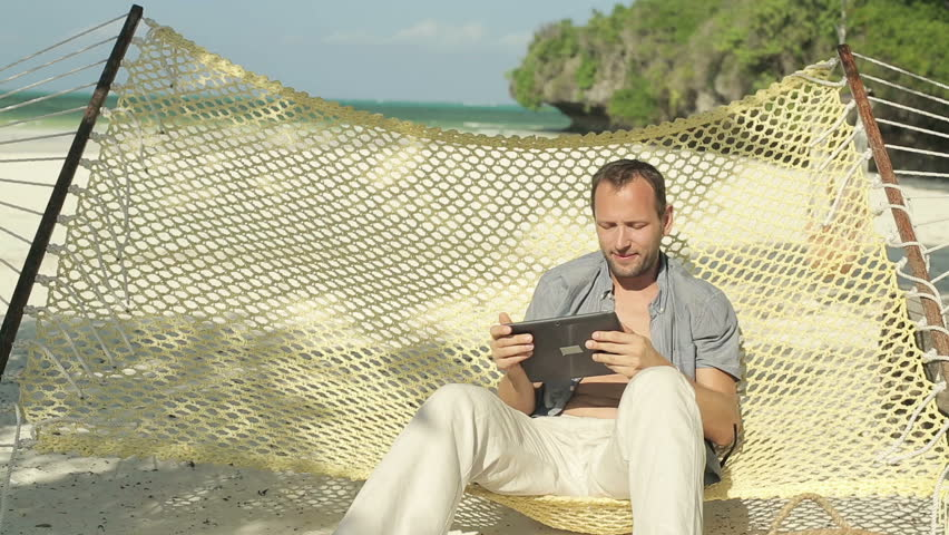 Young man with tablet computer on hammock, exotic beach